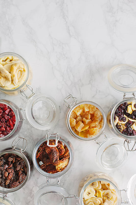 Dehydrated fruits and vegetables in glass jars on white background. by Darren Muir for Stocksy United