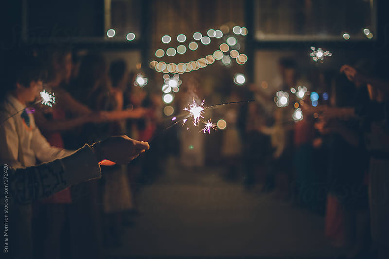 Hand Holding a Sparkler in a Crowd at a Celebration by Briana Morrison for Stocksy United