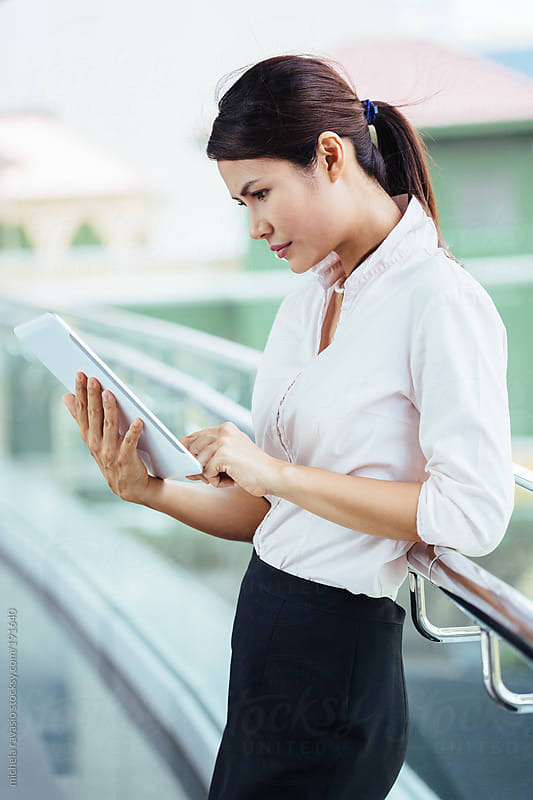 Attractive mature woman using her digital tablet by michela ravasio for Stocksy United