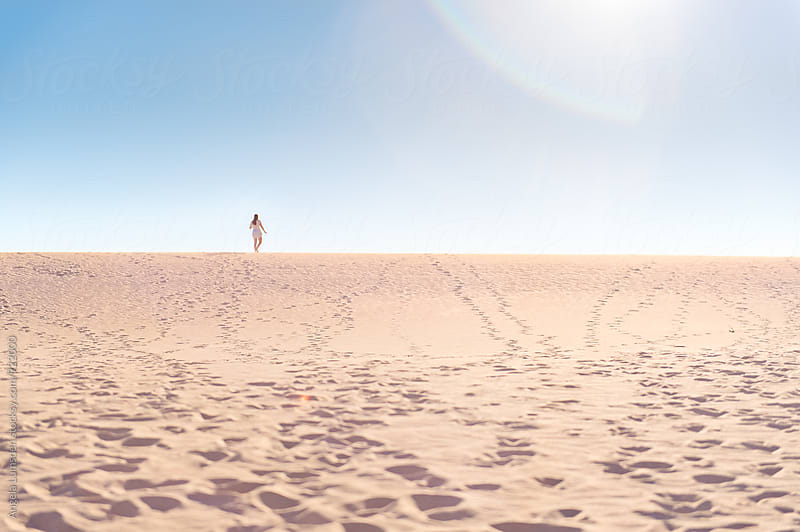 Teenage girl stands small against sand dunes on the Ningaloo Coast in Western Australia by Angela Lumsden for Stocksy United