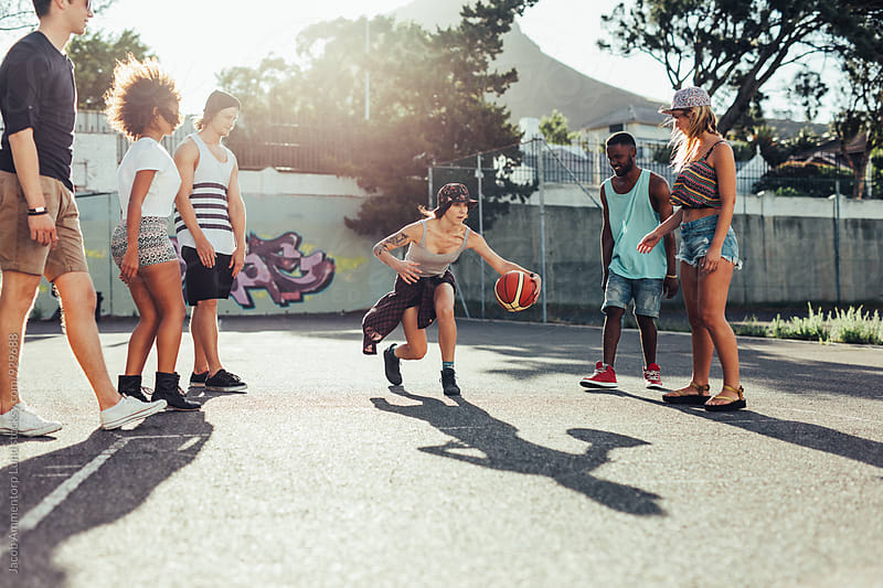 Young girl playing basketball with friends by Jacob Lund for Stocksy United