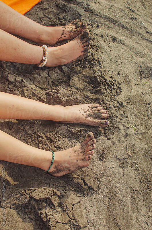 Barefoot feet along a black sand beach by Dominique Chapman for Stocksy United