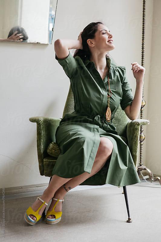 Smiling brunette in khaki dress sitting on chair by Alberto Bogo for Stocksy United