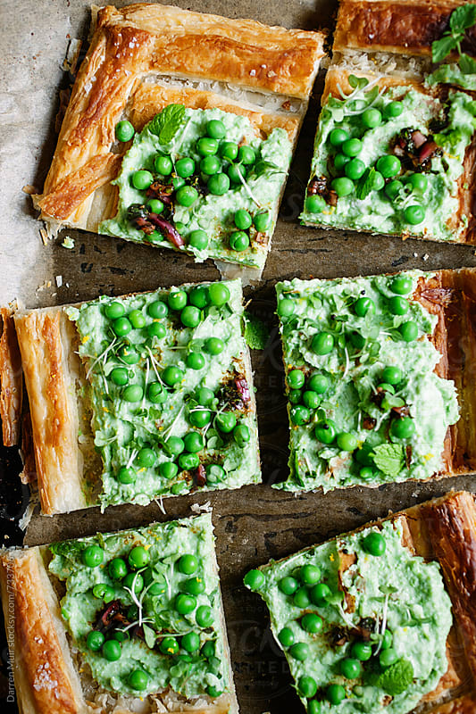 Slices of pea,ricotta and lemon tart on oven tray. by Darren Muir for Stocksy United