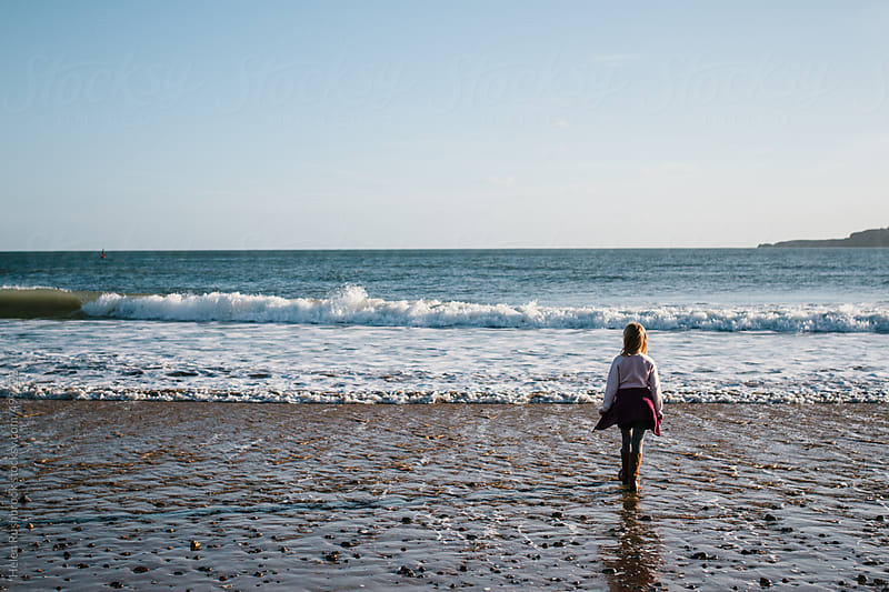 A little girl standing looking at the sea. by Helen Rushbrook for Stocksy United