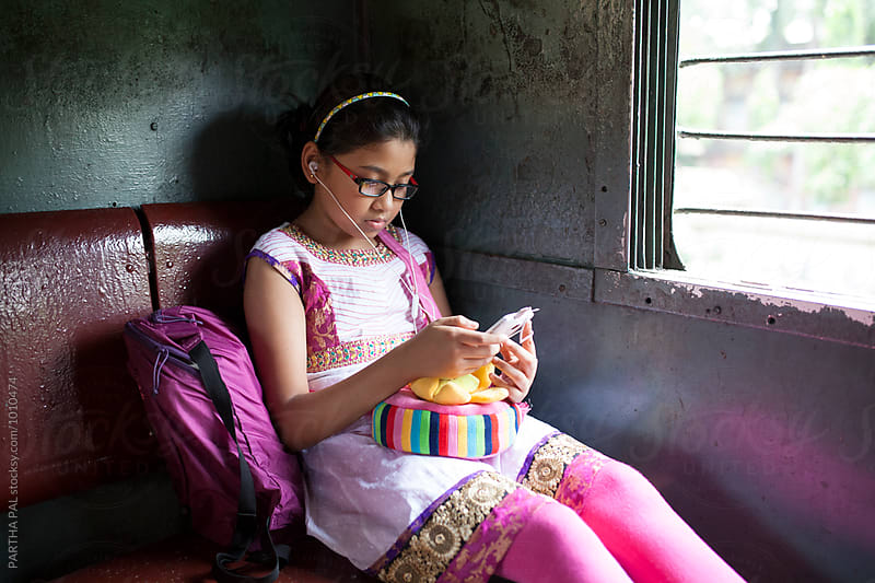 A teenage girl traveling in a local train and using smartphone by PARTHA PAL for Stocksy United