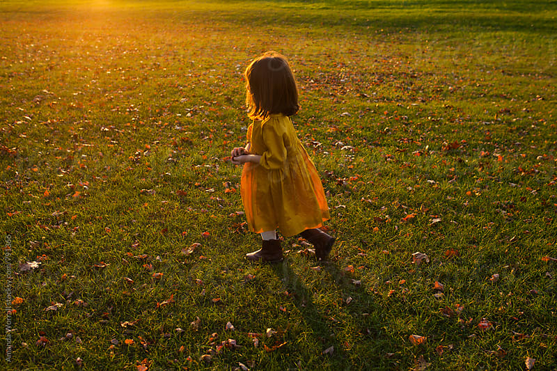Young girl running across a lawn on an autumn evening by Amanda Worrall for Stocksy United