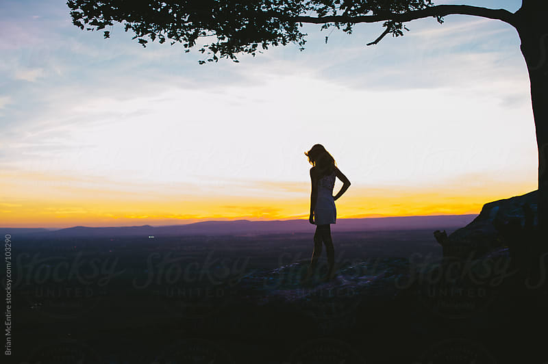 Woman Looks at a Beautiful View from A Cliff Top At Sunset by Brian McEntire for Stocksy United