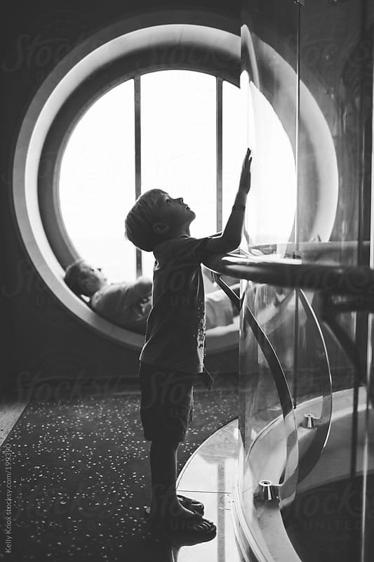 curious child watches a glass elevator by Kelly Knox for Stocksy United