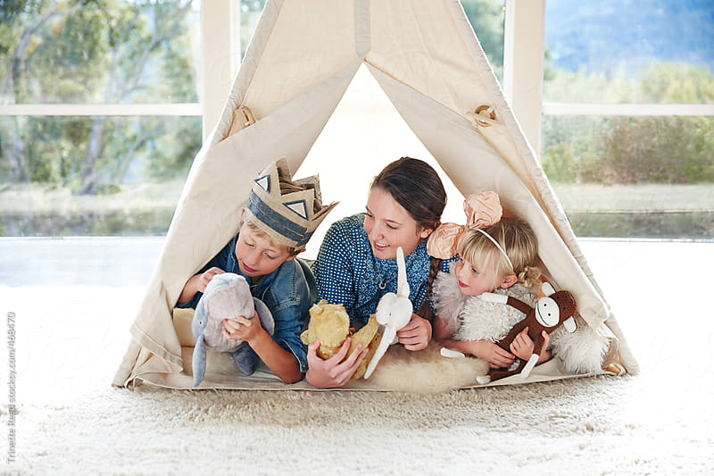 Siblings playing in teepee tent in living room by Trinette Reed for Stocksy United