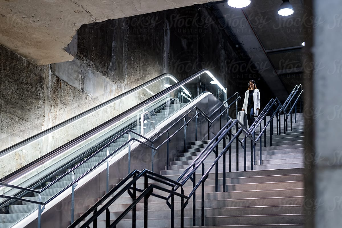 Charmant Female Traveler In Headphones On Moving Stairs By Bisual Studio For Stocksy  United