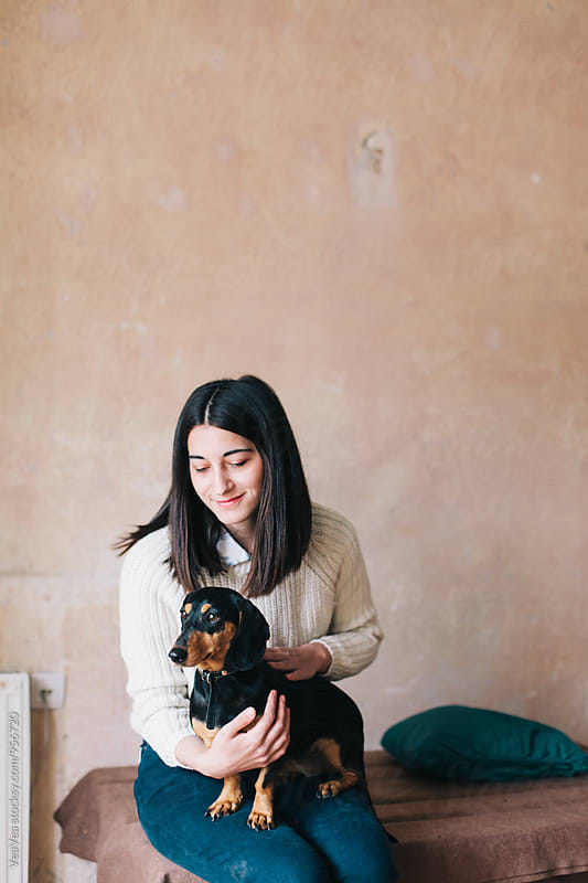 Woman with her dog indoor by Marija Mandic for Stocksy United
