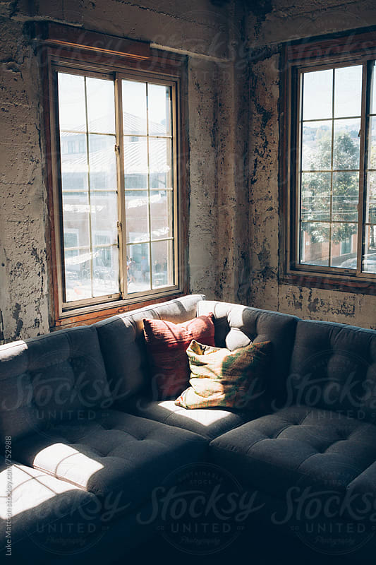 Cozy Corner Couch Near Windows In Rustic Warehouse Attic by Luke Mattson for Stocksy United