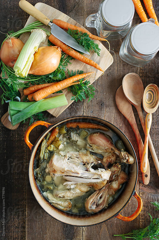 Chicken bone broth: making of bone broth with ingredients. by Darren Muir for Stocksy United