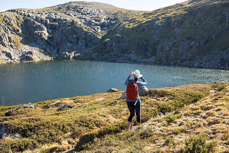A female hiker exploring a glacial lake by Reece McMillan for Stocksy United