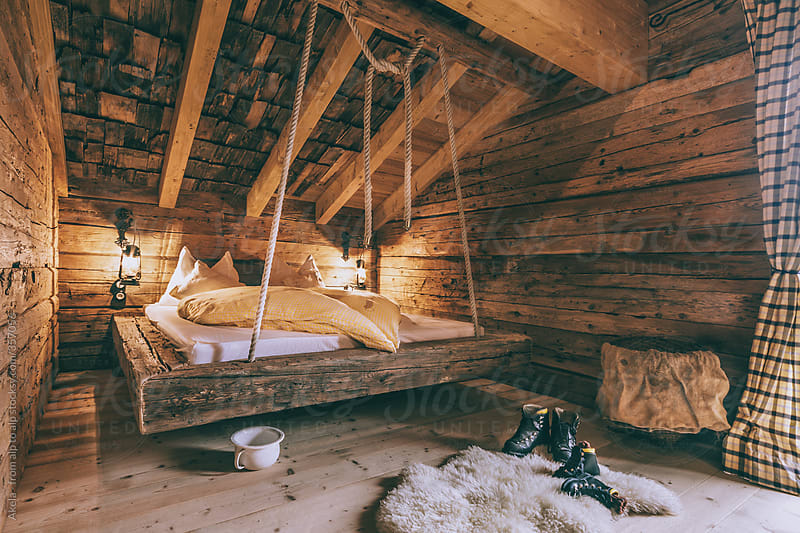 on ropes hanging bed in a typical austrian wooden alpine cabin by leander nardin for stocksy