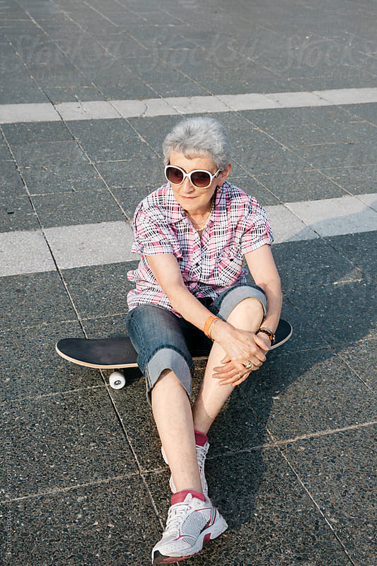 Senior woman sitting on a skateboard alone by Beatrix Boros for Stocksy United