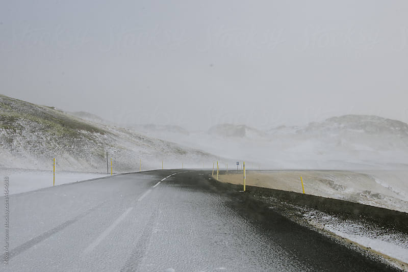 A snow covered road through a dramatic landscape by Mike Marlowe for Stocksy United
