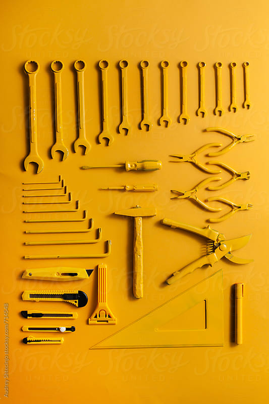 yellow work/handtools of a craftsman on yellow background. by Audrey Shtecinjo for Stocksy United
