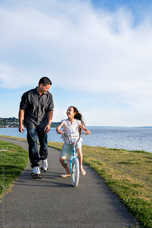 Happy Hispanic father and daughter biking together  by Suprijono Suharjoto for Stocksy United