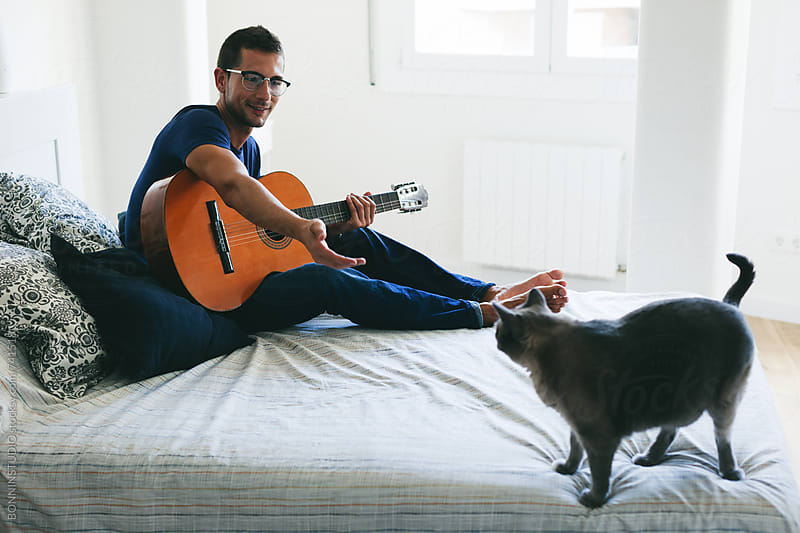 Man playing guitar with his siamese cat on bedroom. by BONNINSTUDIO for Stocksy United