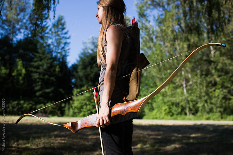 Woman holding bow and arrow by michela ravasio for Stocksy United