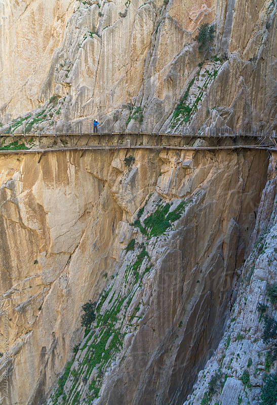 Hiker looking down at the edge of a cliff in Caminito del Rey by ACALU Studio for Stocksy United
