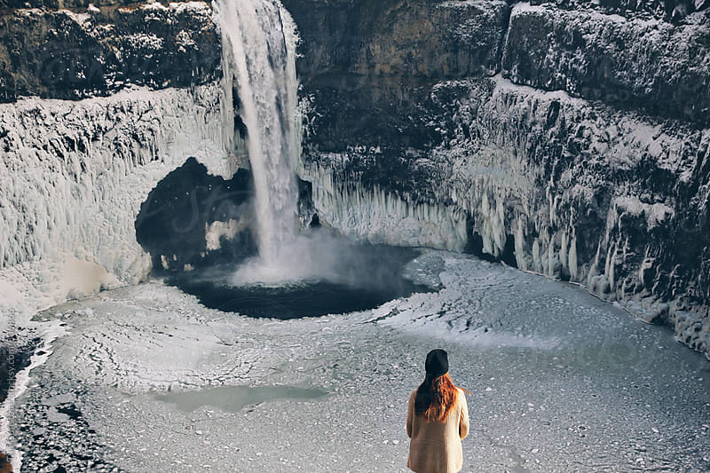 Woman standing in front of icy waterfall by Tari Gunstone for Stocksy United
