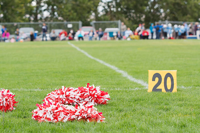 Cheerleading pom poms sit at the 20 yard line of the football field by Tana Teel for Stocksy United
