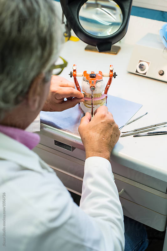 Dental Technician making handmade dental prosthesis in a work shop by Bisual Studio for Stocksy United