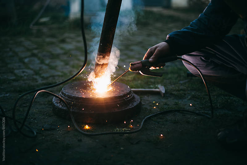 Male hand welding outdoors by Marija Mandic for Stocksy United
