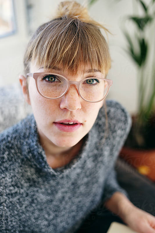 Blonde freckled woman with reading glasses by Lucas Ottone for Stocksy United
