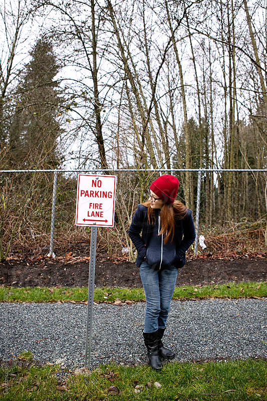 Woman looking at a No Parking, Fire Lane sign along the street by Lawrence del Mundo for Stocksy United