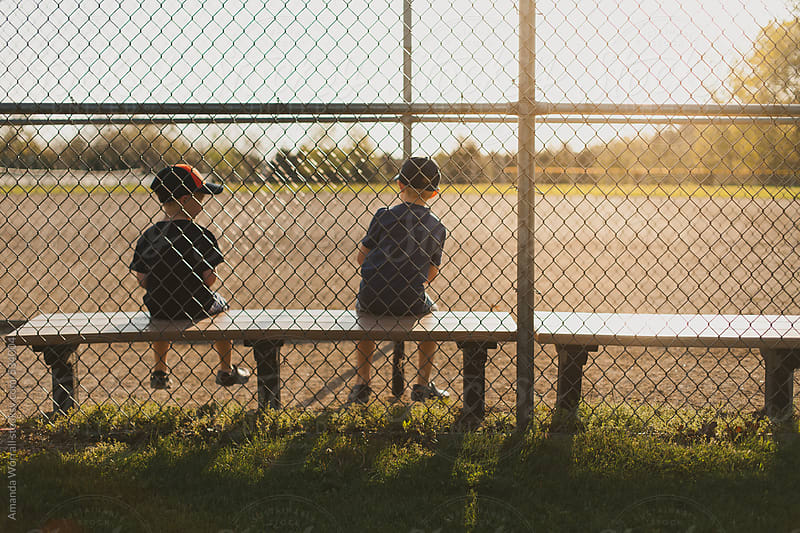 Young brothers sit in dugout looking at empty baseball field at sunset by Amanda Worrall for Stocksy United