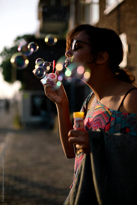 Girl blowing bubbles during sunset by Freek Zonderland for Stocksy United
