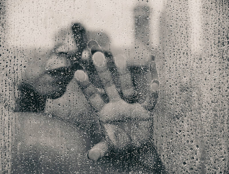 Woman looking out of hot shower, hand on glass by Monica Murphy for Stocksy United