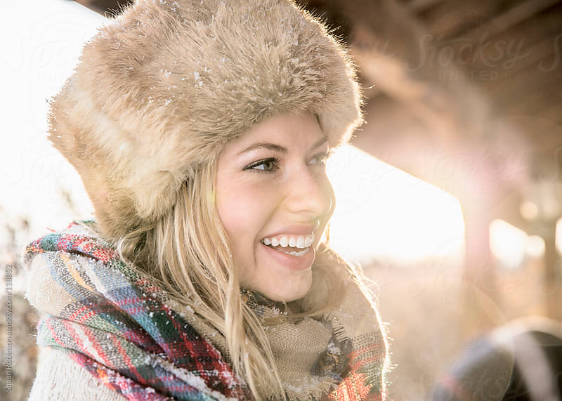 A smiling young woman in a russian hat by Shaun Robinson for Stocksy United