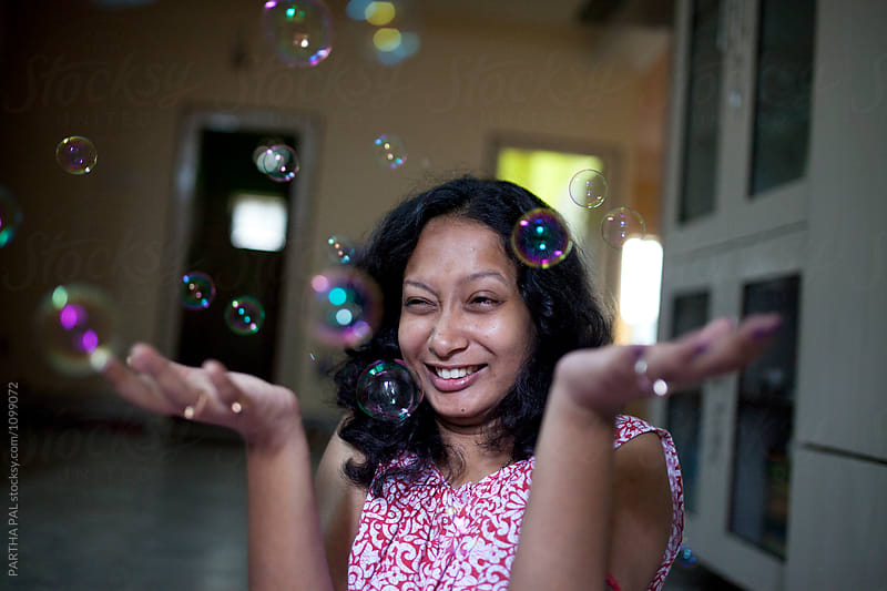 Young woman making fun with bubbles by PARTHA PAL for Stocksy United