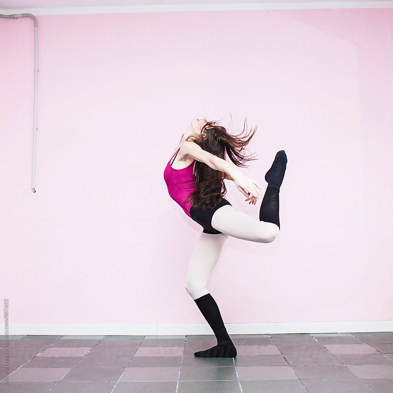 Girl dancing with a pink wall as background by michela ravasio for Stocksy United