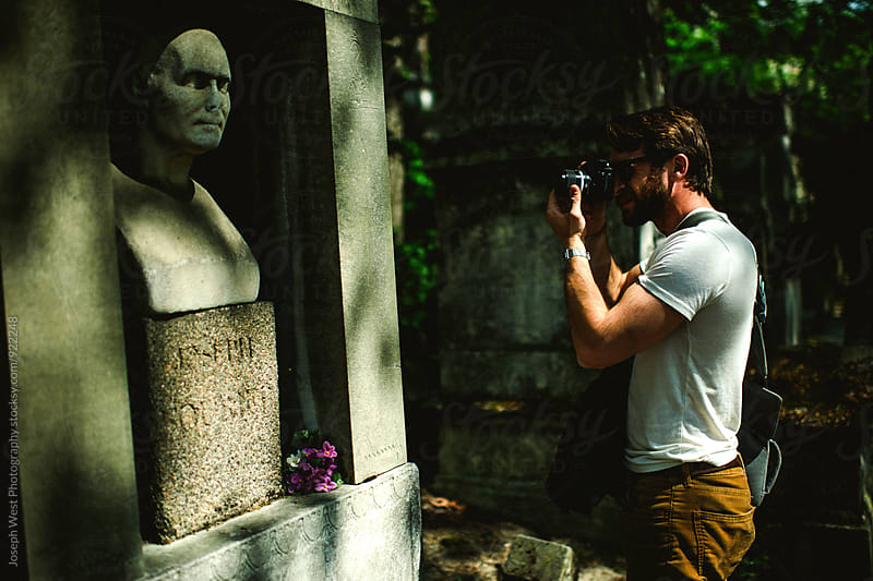 A man photographing a statue by Joseph West Photography for Stocksy United