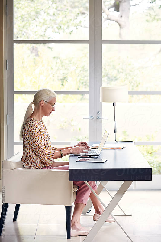Mature businesswoman working in home office by Trinette Reed for Stocksy United