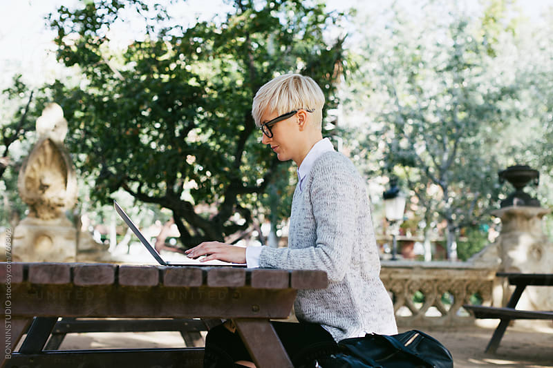 Side view of a woman working on her laptop sitting in the park. by BONNINSTUDIO for Stocksy United