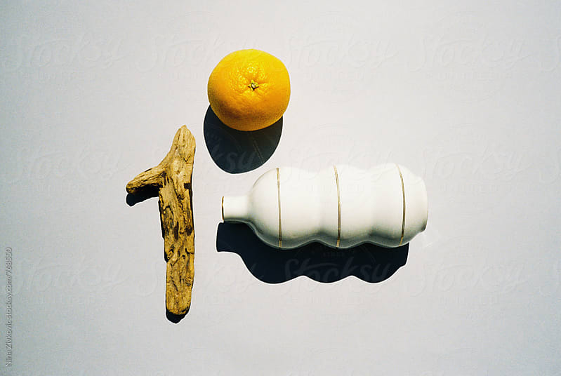 Still life composition with an orange, wood piece and tea pot. by Nina Zivkovic for Stocksy United