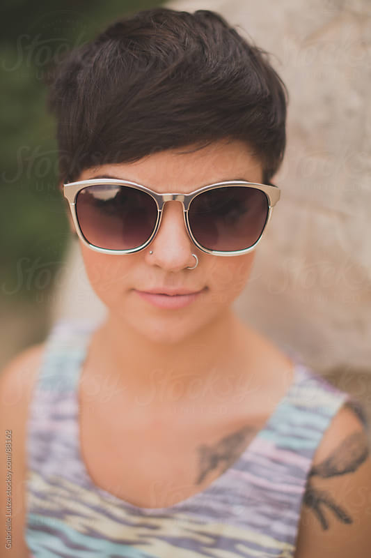 Closeup of short haired edgy girl wearing sunglasses  by Gabrielle Lutze for Stocksy United