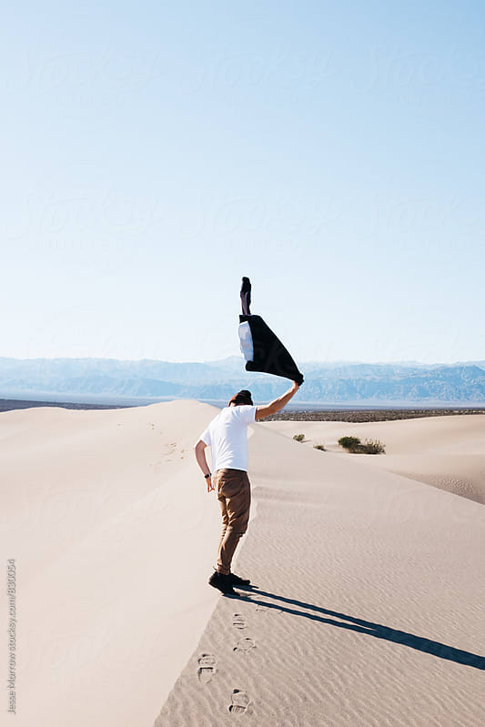 male swinging shirt in wild fashion in desert alone on top of sand dune by Jesse Morrow for Stocksy United