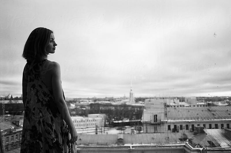 Silhouette of a woman at the window with city view by Liubov Burakova for Stocksy United