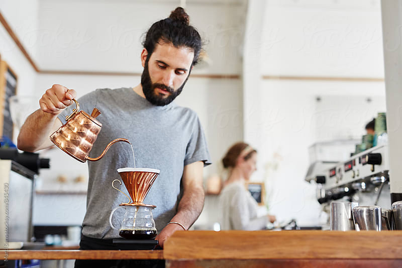 Bearded barista making coffee through chemex by Martí Sans for Stocksy United