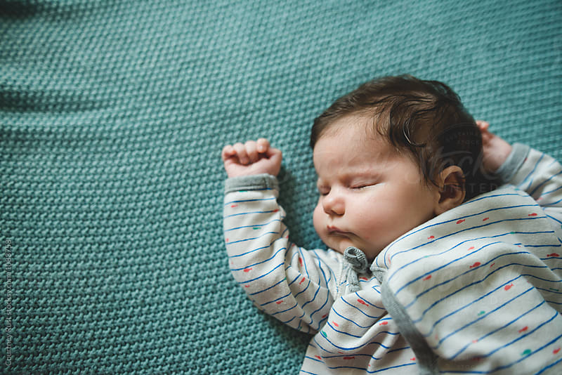 Baby sleeping with arm up by Courtney Rust for Stocksy United