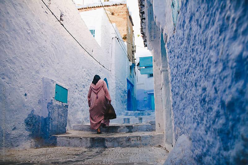 Arab woman in blue medina in Chefchaouen, Morocco by Alejandro Moreno de Carlos for Stocksy United