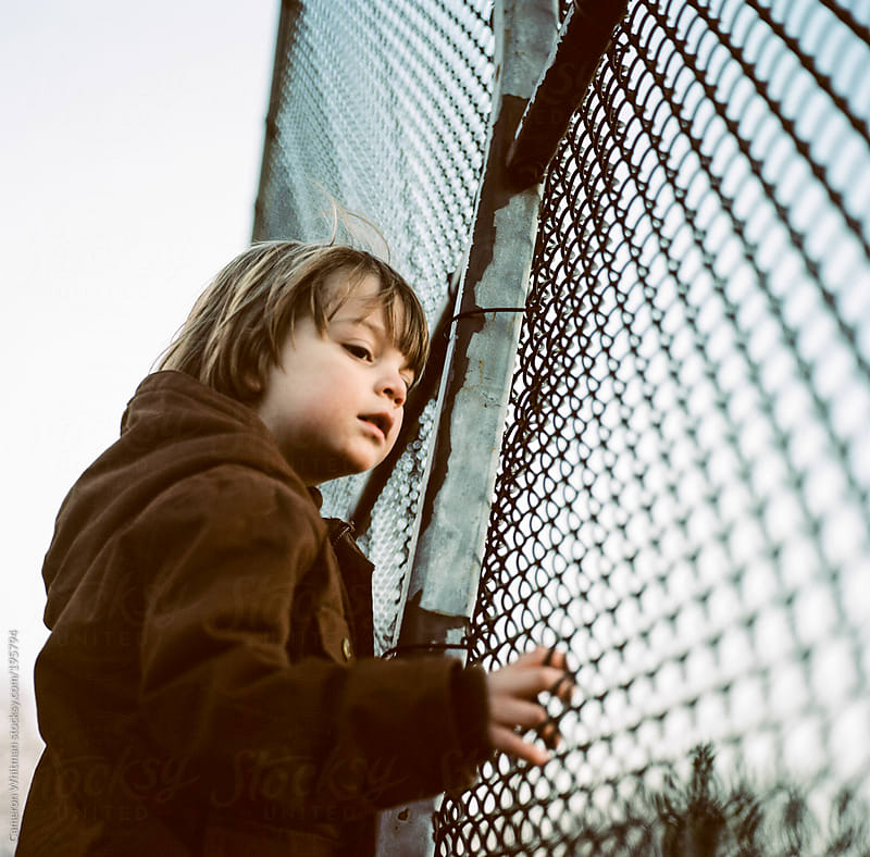 Young boy watching trains through a fence  by Cameron Whitman for Stocksy United